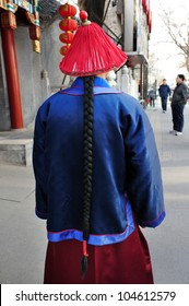 Chinese man wearing a traditional outfit costume outside a restaurant.
