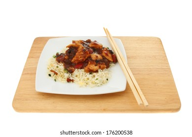 Chinese meal, chicken in black bean sauce with egg rice, chopsticks at the side of the plate on a wooden board isolated against white
