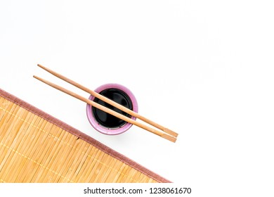 Chinese meal concept. soy sauce in bowl near chopsticks and bamboo table mat on white background top view space for text pattern