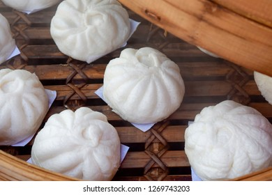 Chinese meat buns, Chinese steamed pork bun, baozi, steamed buns with pork,  pork bao, in bamboo steamer container.