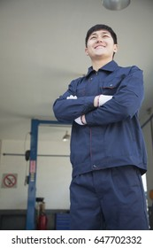 Chinese mechanic standing with arms crossed