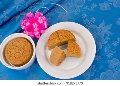 Chinese moon cake in white plate on blue table cloth.