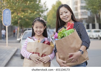 Chinese mother and daughter carrying bags of groceries