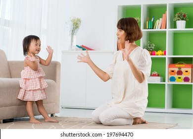 Chinese mother and daughter playing clapping game