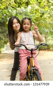 chinese mother having good time on bicycle with her daughter outdoor, peace sign