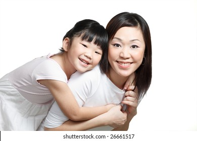 Chinese mother piggyback daughter smiling happily. Isolated in white.