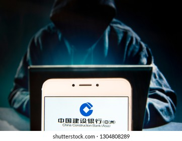 Chinese multinational banking company China Construction Bank Corporation (CCB) logo is seen on an Android mobile device with a figure of hacker in the background.