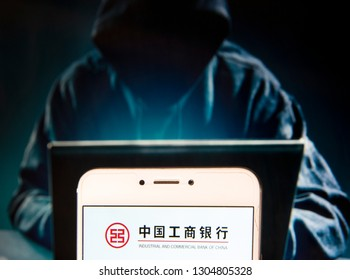 Chinese multinational banking company and largest bank in the world Industrial and Commercial Bank of China (ICBC) logo is seen on an Android mobile device with a figure of hacker in the background.