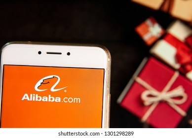 Chinese multinational conglomerate specializing in e-commerce, retail, Internet, AI and technology Alibaba logo is seen on an Android mobile device with a Christmas wrapped gifts in the background.