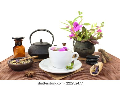 Chinese natural medicine with a cup of tea, flower petals and herbs