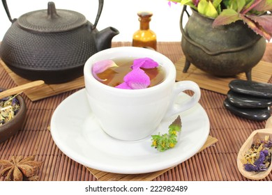 Chinese natural medicine with a cup of tea and flower petals and stones