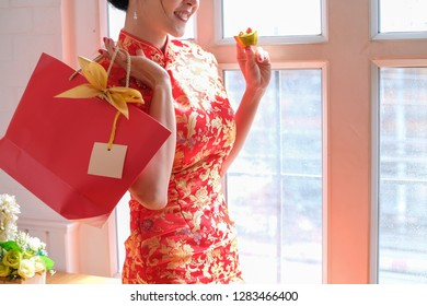 Chinese new year. Asian woman wear cheongsam red holding gold bar and shopping bag.