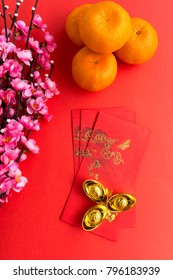 Chinese New Year background concept - Mandarin Orange, Red Envelopes, Plum Flowers and Gold Ingots with Chinese Character Happiness and Prosperity.