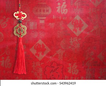 Chinese New Year background. Chinese good luck symbol isolated on red silk fabric with text and sign.