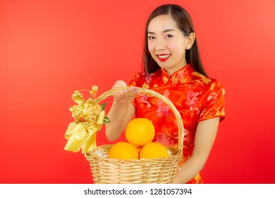 chinese new year beautiful happy teeth smile asia chiness girl ware Qipao Oriental Chic Cheongsam traditional dress holding lucky orange with red background copy space isolated.