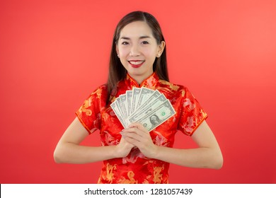 chinese new year beautiful happy teeth smile asia chiness girl ware Qipao Oriental Chic Cheongsam tradition dress holding bank note with red background copy space isolated