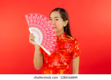 chinese new year beautiful happy smiley asia chiness girl ware Qipao Oriental Chic Cheongsam holding fan with red background copy space isolated