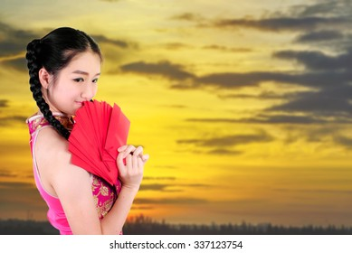 Chinese new year. beautiful young Asian woman dress traditional cheongsam holding red envelopes with blurry sun set background