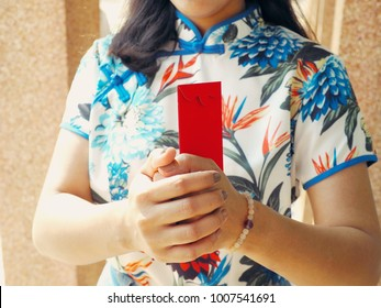 Chinese New Year celebrations with red envelope in hands of woman wearing cheongsam or qipao - Chinese traditional dress. Concept image for Lunar New Year or Spring Festival 2018.