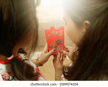 Chinese New Year celebrations with red envelopes in hands of women wearing Chinese traditional blouse. The Chinese blessing word means everything you do will be smoothly! Concept for Lunar New Year.