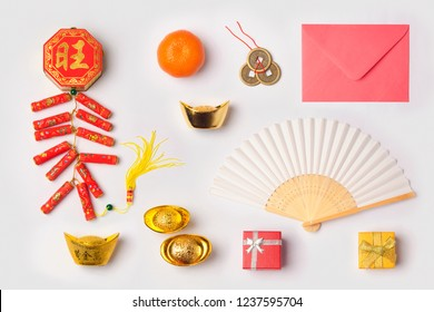 Chinese New Year concept with traditional decorations for Spring festival organized on white background. Top view from above. Chinese text: fortune, good luck and wealth.