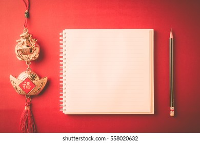 chinese new year decoration and blank note book on red paper background