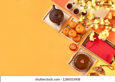 Chinese New Year decoration and food. Orange, tea, new year cake, red packet, fire cracker, plum blossom and lantern on color paper background. Translation of text appear in image: Prosperity