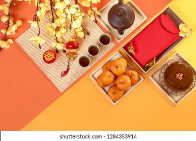 Chinese New Year decoration and food. Orange, tea, new year cake, red packet, plum blossom and lantern on color paper background. Translation of text appear in image: Prosperity