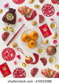 "Chinese new year decoration items, food and drinks on white background. Flat lay image. ""Prosperity"" word is printed on red packet and tangerine sticker."