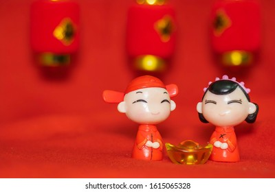Chinese New Year decoration on a red background Chinese Couple Figure Model wish for a Luck  and lump of gold and a Chinese Word on Lantern said Luck