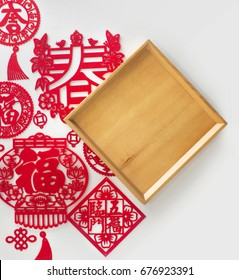 "Chinese new year decorations and wooden empty tray text space background. ""Spring"",""Prosperity"" and ""Lucky"" words cut out from red paper. Traditional Chinese art and craft paper cutting."