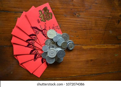 Chinese New Year envelopes bearing the symbol  'happiness' fanned out on wooden table and held in place by coins space for copy