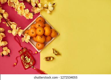 Chinese New Year festival decoration. Orange,plum blossom, money red bag and gold 'yuan boa'  on red and yellow background. Translation of text appear in image: Prosperity