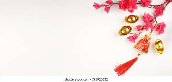Chinese New Year flat lay background with assorted festival decorations. Chinese characters on gold ingot means abundant of wealth.