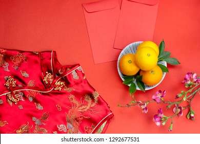 Chinese new year fresh oranges and angpao pocket and qipao and cherry blossom branch border on red paper background