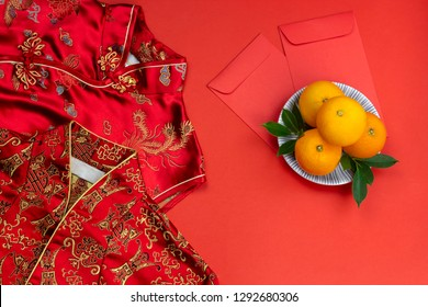 Chinese new year fresh oranges and angpao pocket and qipao on red paper background