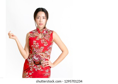 Chinese new year gold ingots in Beautiful Smiling Young Asian Woman hand in red cheongsam dress, chinese new year concept. Asian cheerful, lovely woman in chinese dress traditional cheongsam.