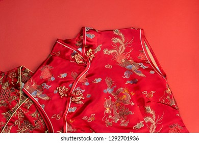 Chinese new year red male and female qipao on red paper background