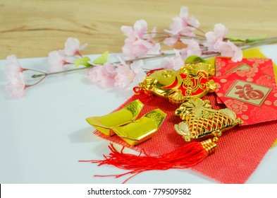 Chinese New year and traditional holiday cerebration for rich gold and swimming fish, golden money, pink flowers, red envelope with text meaning good luck on red, yellow cloth and white background