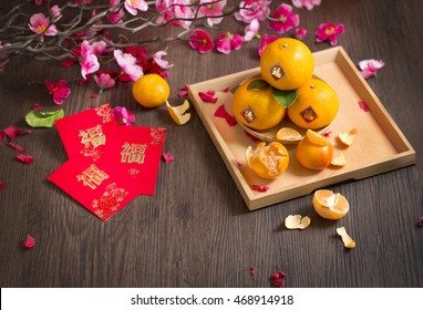 """Chinese new year wooden table top shot with red packet printed with word """"Blessing"""" and tangerine oranges."""