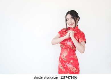 Chinese New Year.Asian women in traditional Chinese cheongsam dresses with greetings and welcomed gestures on a white background.