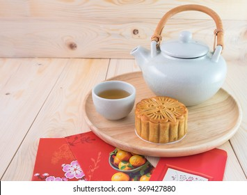 Chinese new year,mooncake with a cup of tea on wooden dish and money in red packets