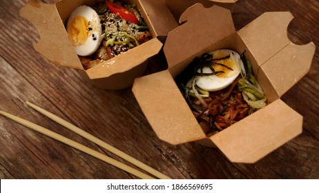 Chinese noodles with chicken and vegetables in cardboard boxes on a wooden background, Asian food delivery, concept of street food, copy space