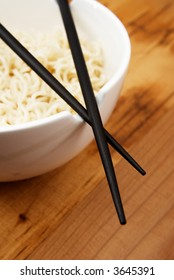 Chinese noodles with chop sticks in a bowl on wooden counter