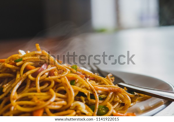Chinese Noodles, Chowmein on a Plate with Spoon and Fork,Hot and Fresh Chow Mein in Nepali Style