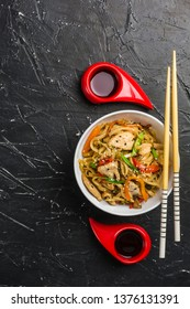 Chinese noodles in a Cup with chicken and vegetables with sticks. Wok food from the restaurant on a dark background from a top view.