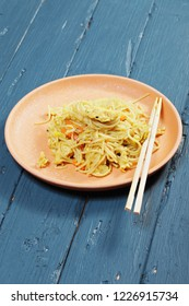 Chinese noodles in plate over blue wooden board. Vertical shot