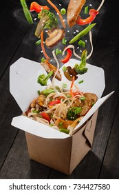Chinese noodles with vegetables. Ingredients are falling into box: noodles, chicken meat, mushrooms, broccoli, pepper, lettuce, asparagus and sesame seeds. Presentative photo of food product.