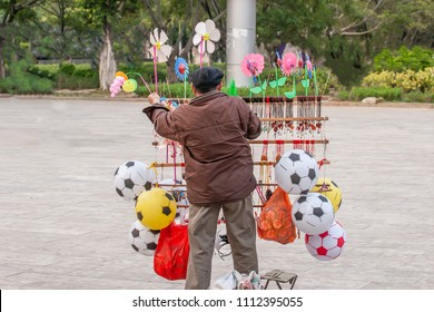 Chinese old man street vendor seller ball and other toys in the Public garden of Nansa, Yunnan, China. Football Games concept.