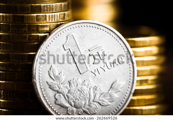 Chinese One Yuan Coin  and gold money on the desk. Peony flower depicted in the Chinese one Yuan coin.